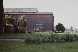 The photo shows probably the first artistic mural in Poland, made by Christian Wabl in 1973, during the Fifth Biennial of Spatial Forms in Elbląg. The mural showing a letter to the people made of flowers' pictographs instead of letters of the alphabet was painted on the wall of the Mechanical Works Zamech company. Photo by KwieKulik.