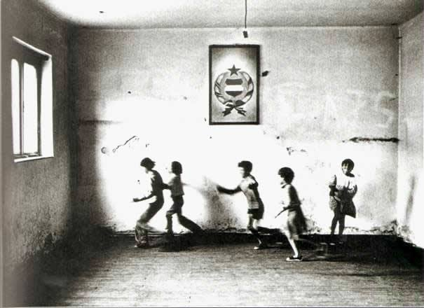 An empty room of a rundown village school with playing children, Tólápa, Hungary 1982