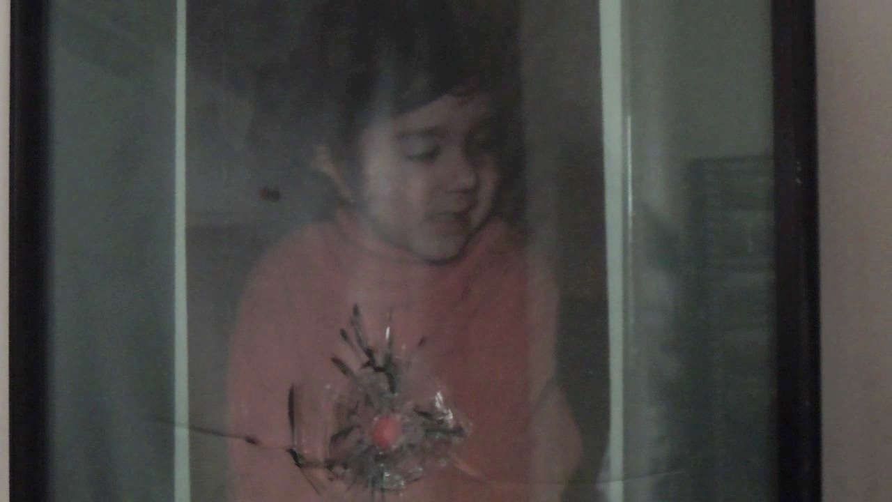 Picture of Cristina Lungu, the youngest victim of the revolution, behind a window glass with a bullet hole