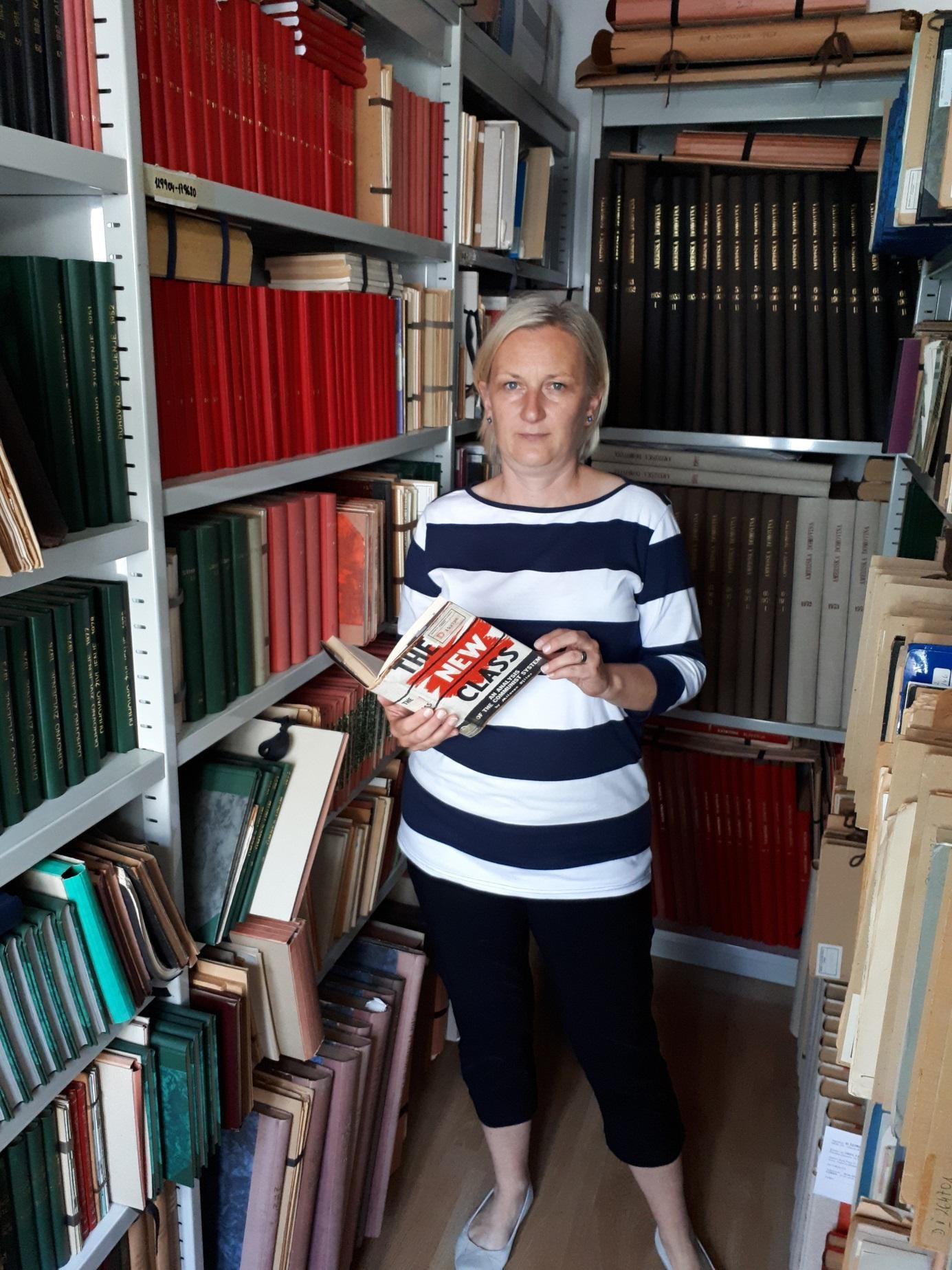 Helena Janežič in v ozadju D fond, ki se nahaja v sklopu Zbirke slovenskega tiska izven Republike Slovenije v Narodni in univerzitetni knjižnici v Ljubljani (2018-05-24).